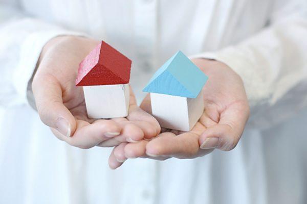 中古と新築二つの家の形をした積み木を両手ですくっている画像です。